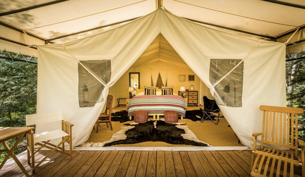 A luxury tent with a bedroom suite inside.