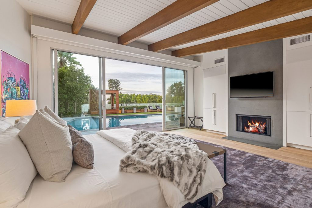 A bedroom with a fireplace, wooden beams on the ceiling, and a view of the backyard pool.