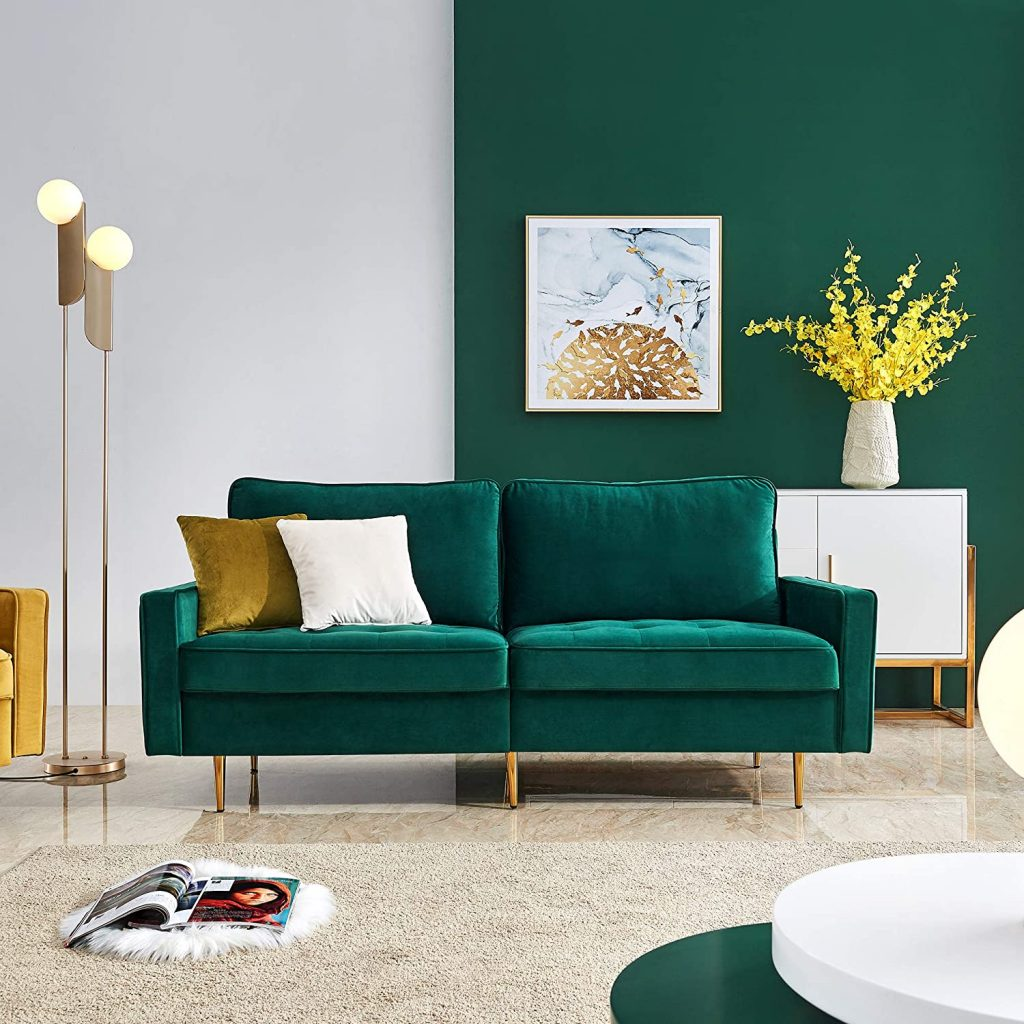 A living room with green velvet sofa with gold legs.