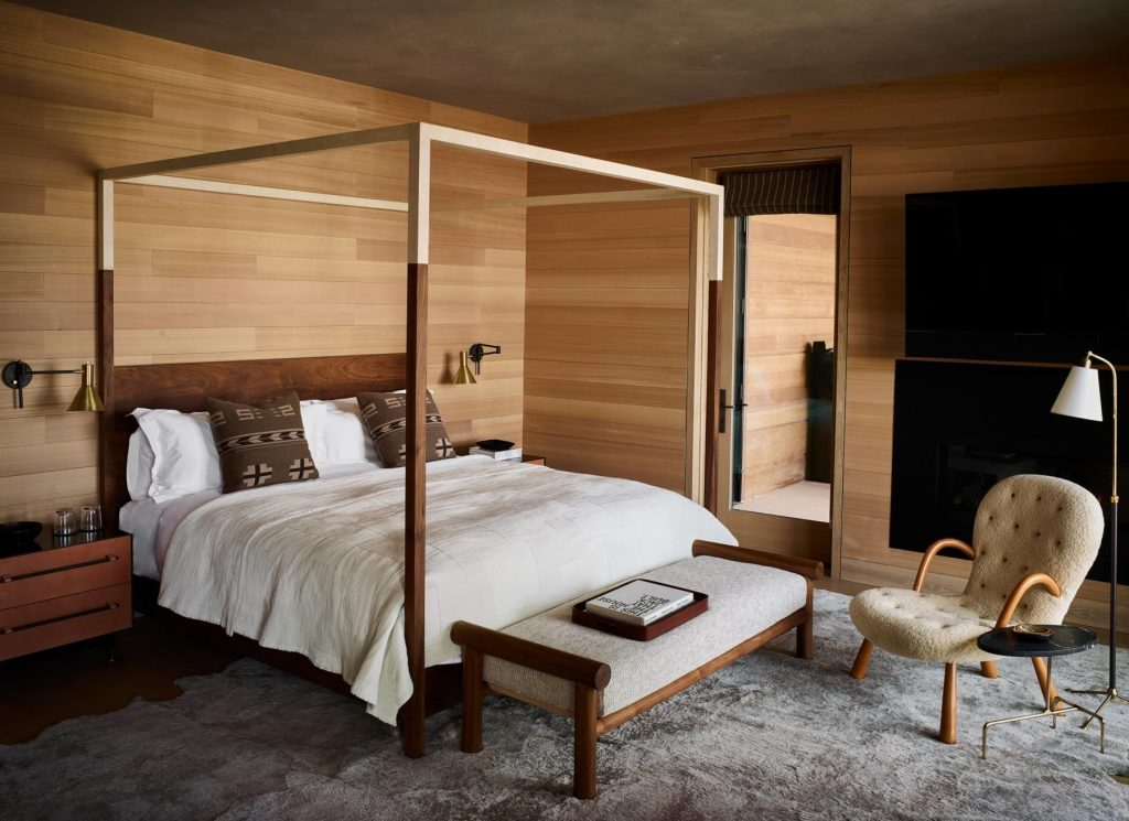 Hotel room at Caldera house with smooth wooden walls and canopy bed.