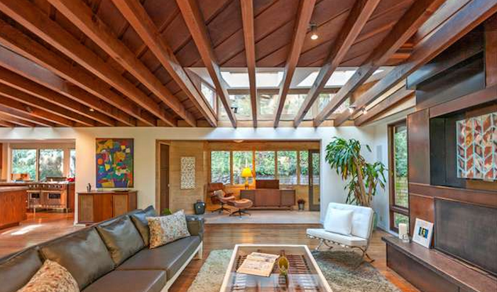 A living room with a large sofa with wooden beams and skylights on the ceiling.