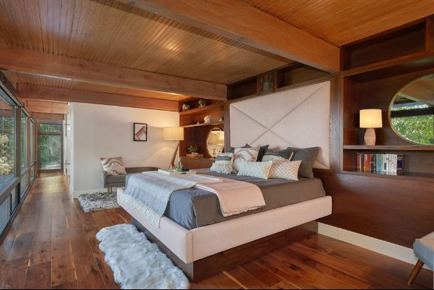 Large bedroom with wooden floors, wooden ceiling beams, and floor to ceiling view of outdoor greenery.