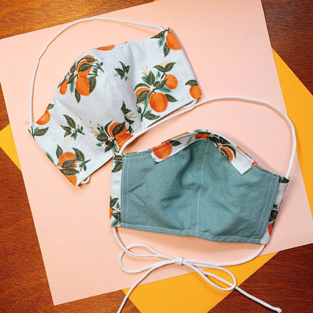 Front and back view of a mask with orange fruit print.