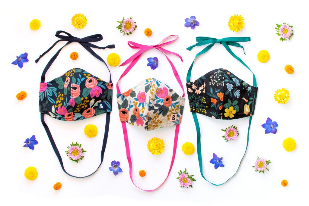 Three face masks with Rifle Paper Co. floral prints and flowers around it.
