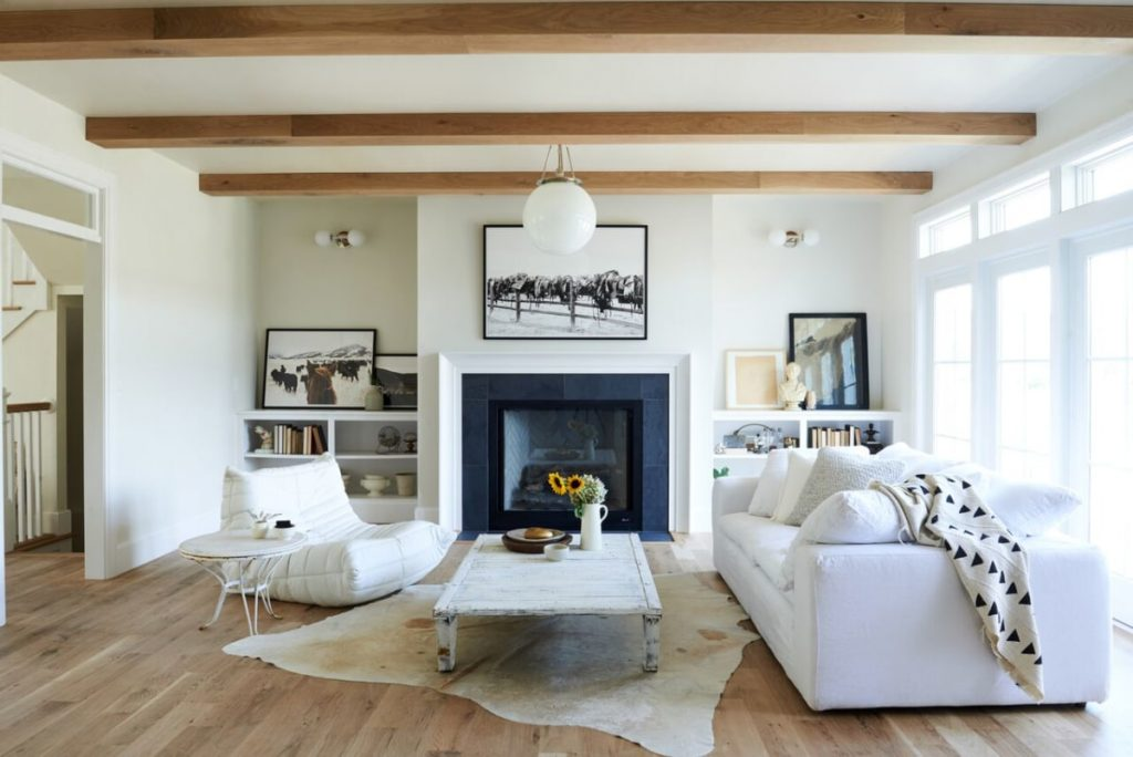 Living room with warm white walls with wooden floors and wooden beams on the ceiling.