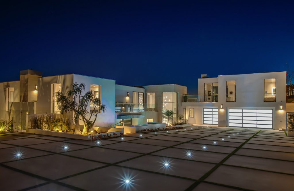 Exterior of luxury home with beautiful lighting and landscaping.