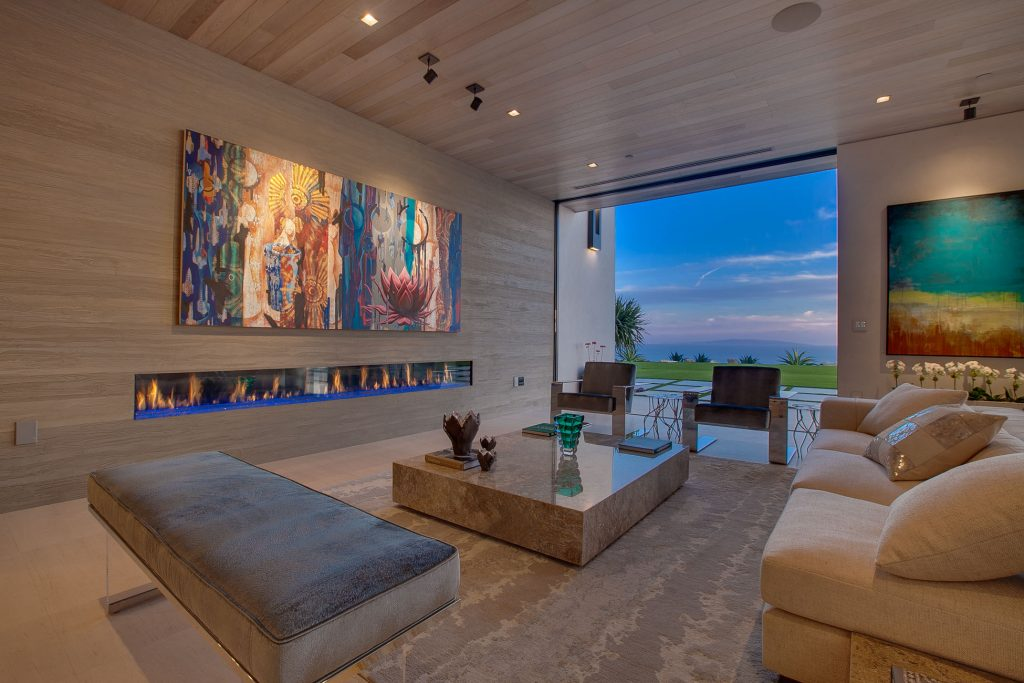 Living room area with large colorful painting above long fireplace, marble table, sofa, and beautiful view.