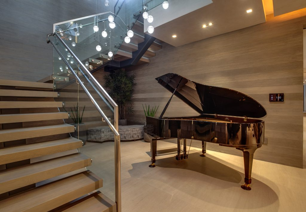 A beautiful black grand piano nearby the staircase.