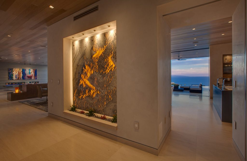 An art piece encased in the wall beautifully lit with plants lining the bottom.