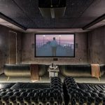 At home movie theater with projector screen with luxurious black furniture