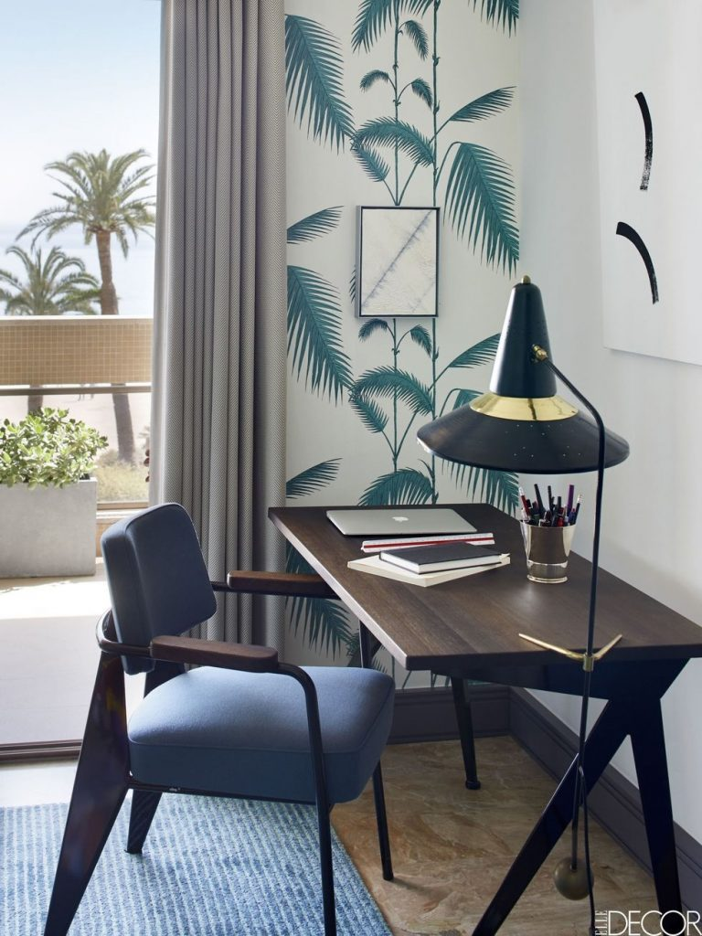 Home office with desk, sturdy chair, lamp, blue rug, and palm wallpaper nearby a window.