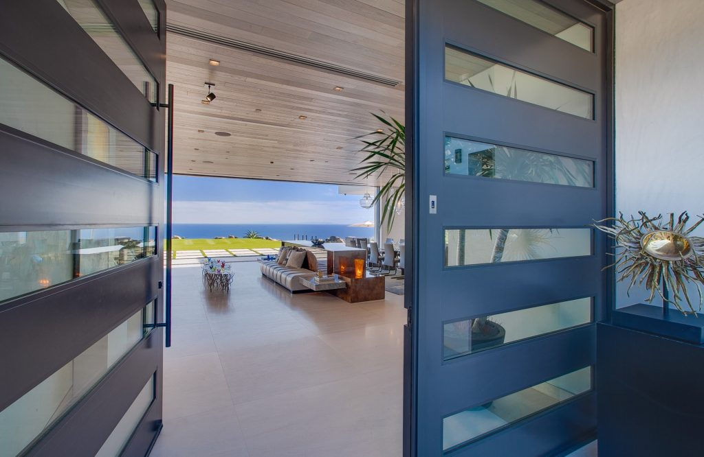 Front doors opening up to an open floor plan with views of the water.