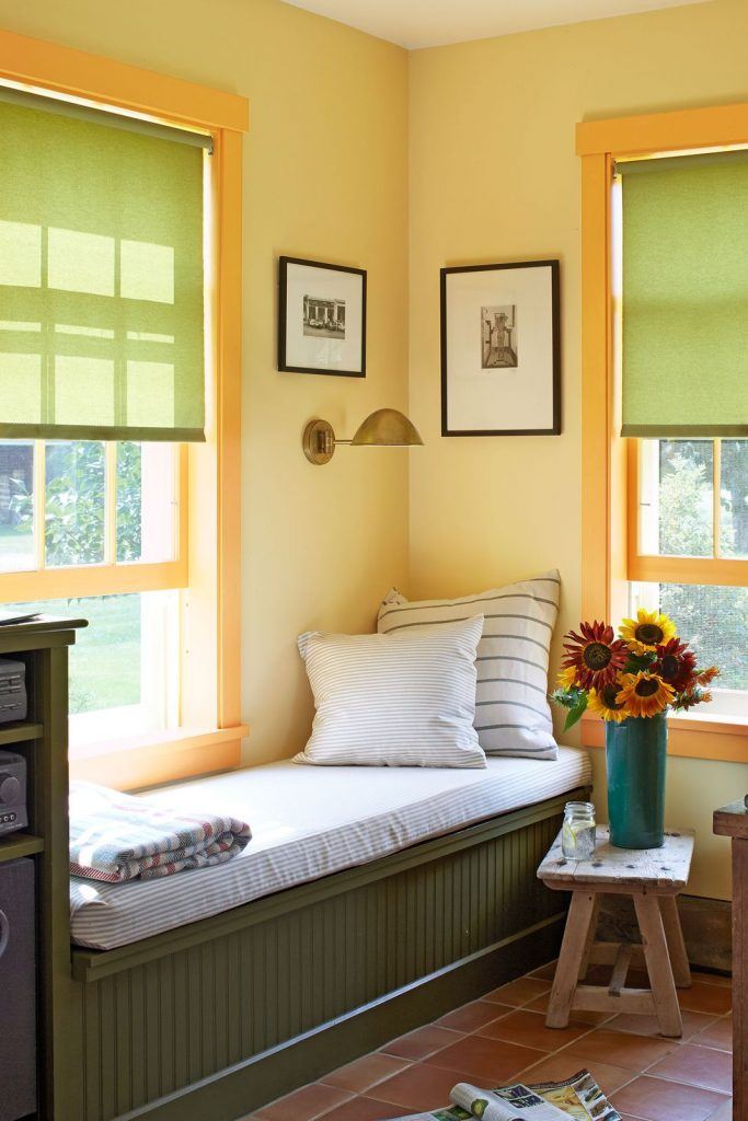 Reading nook by windows, yellow walls, green built in seating with throw pillows, blanket, and a vase of flowers nearby.