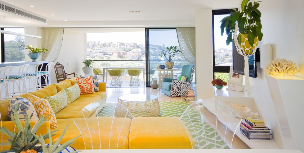 Bright and cheerful living room with yellow sectional, throw pillows, hanging plant, and floor to ceiling window views.