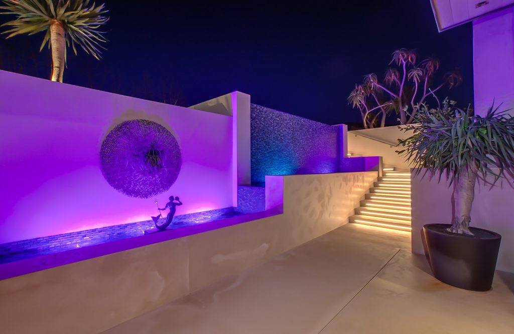 Water feature of home with blue lighting next to a beautifully lit stairway.