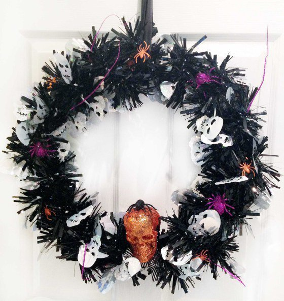A black halloween themed wreath with skulls and spiders.