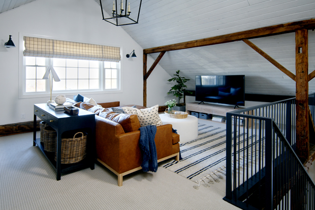 Living area with angled white ceiling, gorgeous wood beams, leather couch, and TV.