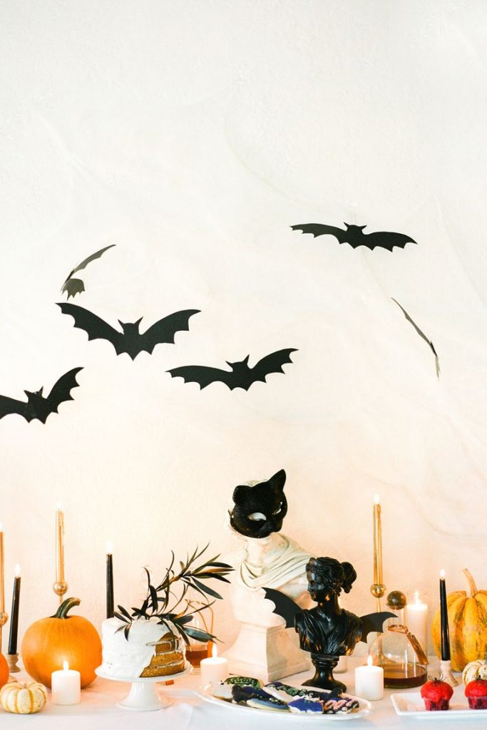 A tablescape with candles, candlesticks, pumpkins, and bat cutouts hanging from the ceiling.