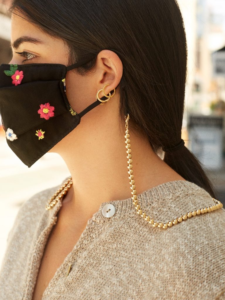 Close-up of a girl wearing a black mask and gold beaded mask chain.