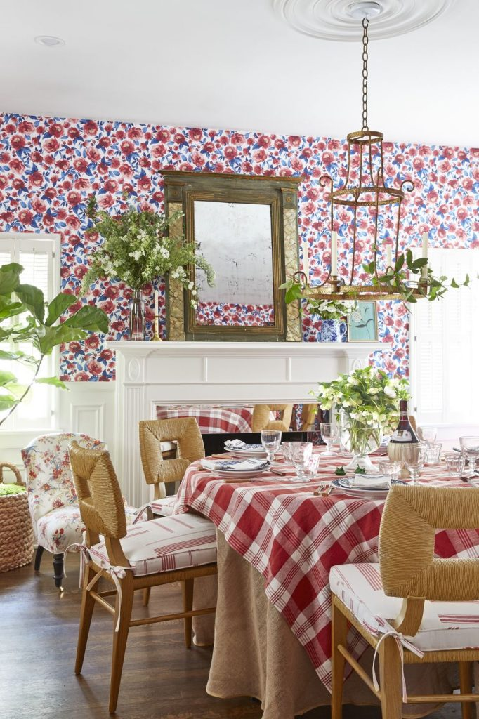 A charming dining room with bright floral wallpaper, and red plaid tablecloth.