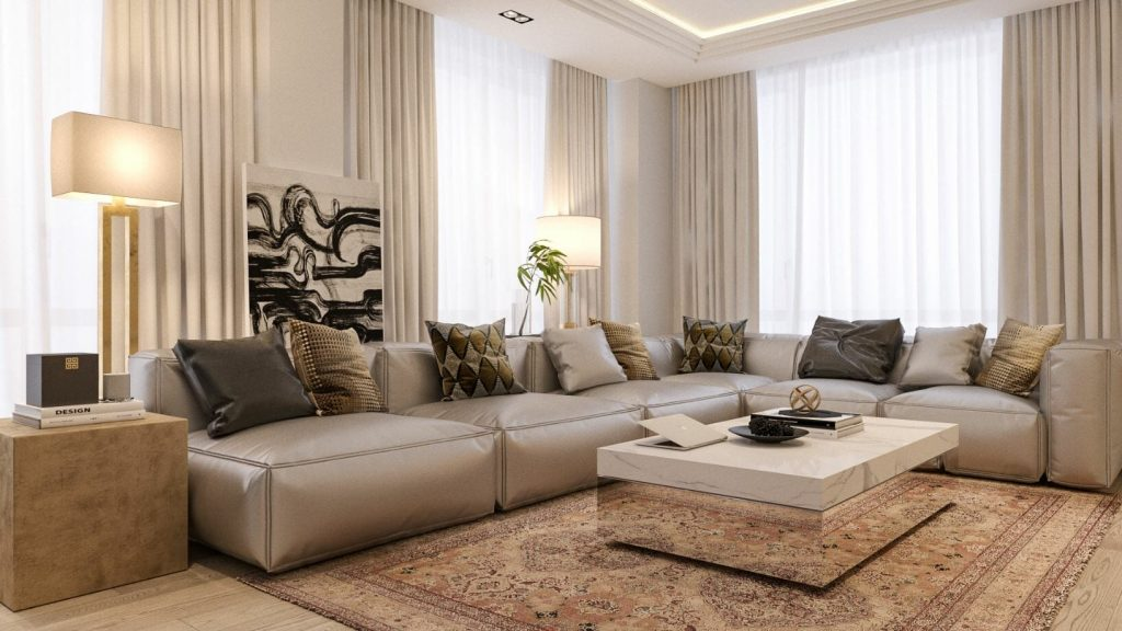 A contemporary style living room with gray sectional and reflective coffee table.