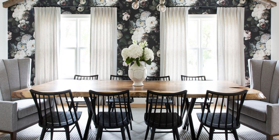 A dining room with dark floral wallpaper balanced with white curtains.