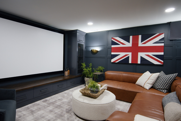 A home theater with a large screen,  navy-paneled walls, cognac leather sectional, and framed British flag.