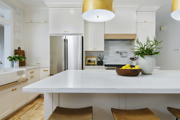 All-white kitchen with gold fixtures, large island, and stunning gray and white tile backsplash.