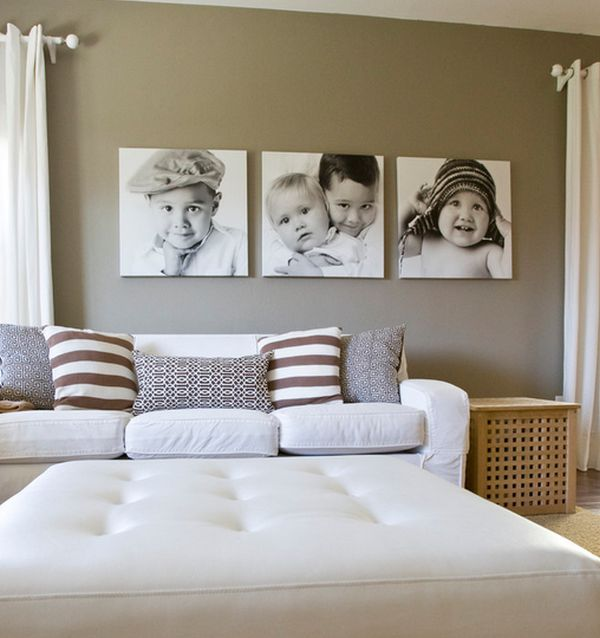 A neutral colored living room with black and white photographs of children on the wall.
