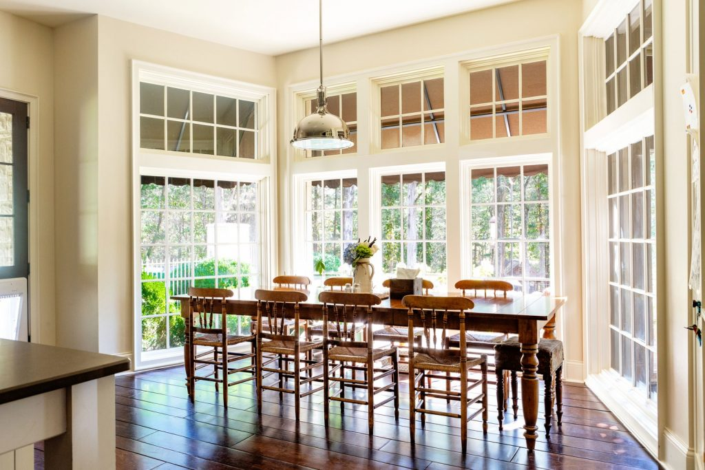 Dining room surrounded by white floor to ceiling windows.