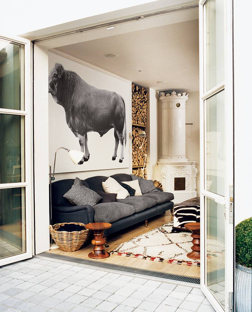 A bohemian style living room with oversized black and white portrait of a farm animal.