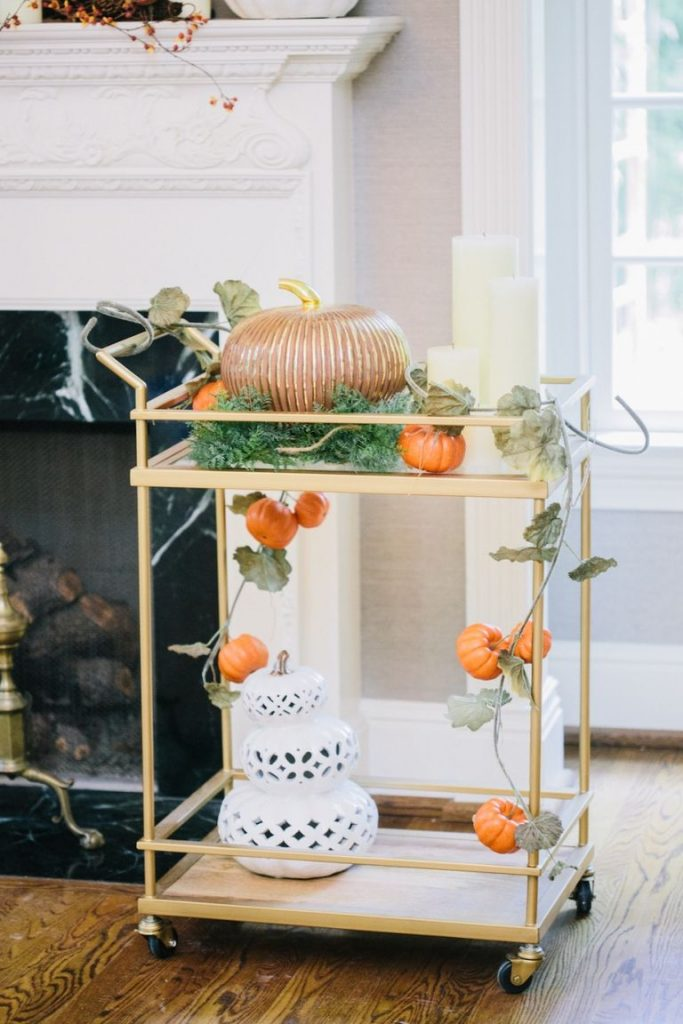 A gold bar cart decorated with different pumpkin figurines and pumpkin garland wrapped around.