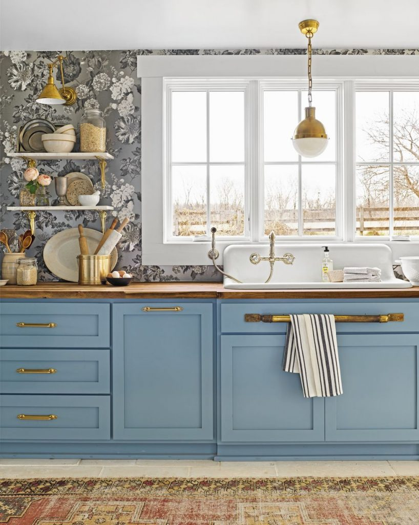 A dreamy kitchen with blue cabinetry, wooden countertops, and gray and white floral wallpaper.