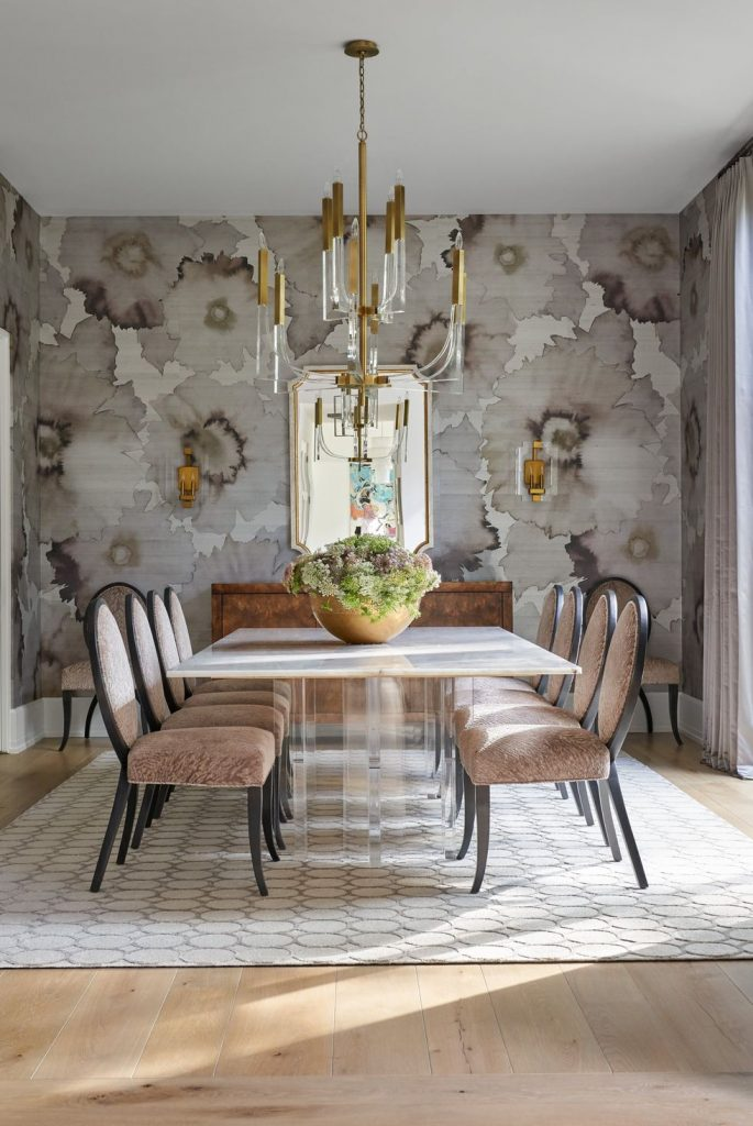 A sophisticated and stylish dining room with grayscale, floral wallpaper.