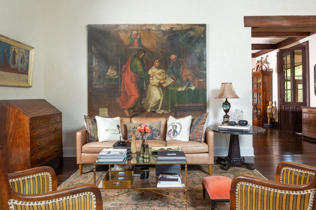 Formal living room with religious oil painting on the wall behind a leather couch.