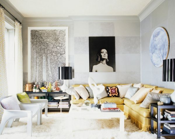 Cozy living room with yellow couch, white rug, and black and white portrait on the wall.