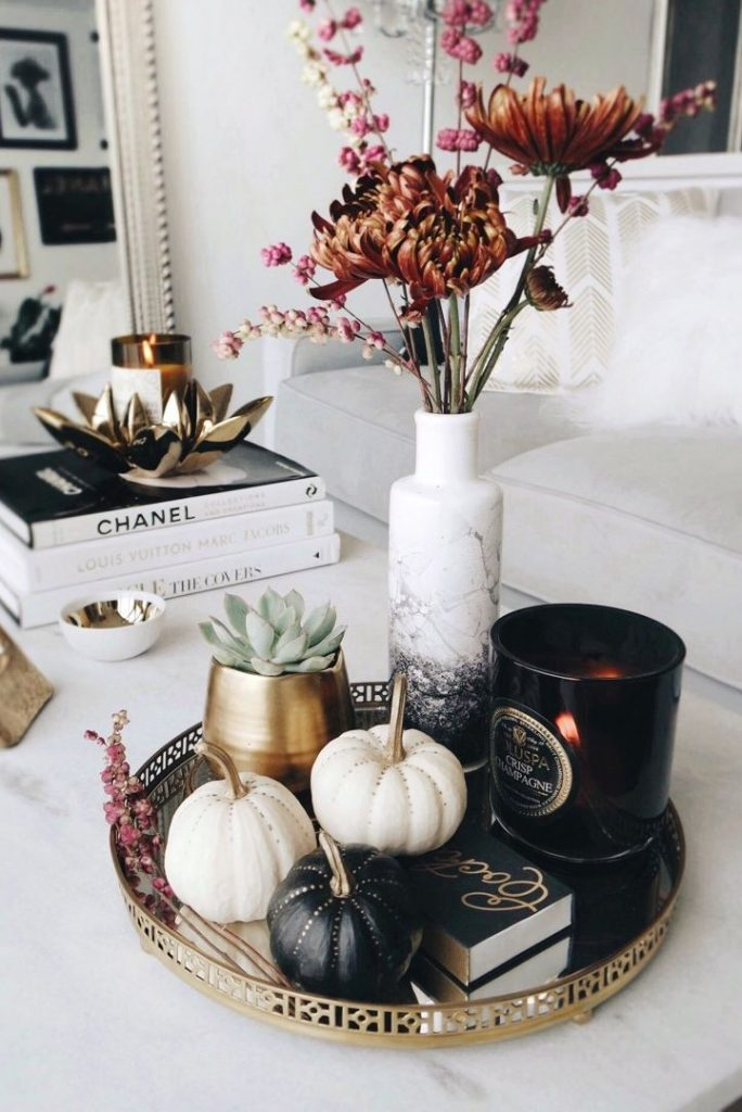 Vignette on gold tray with black and gold pumpkins, gothic style candle, succulent, and vase of flowers.