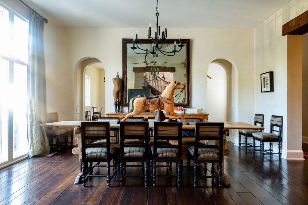 Formal dining room with toy horse on table, large vintage mirror, and vintage chandelier.