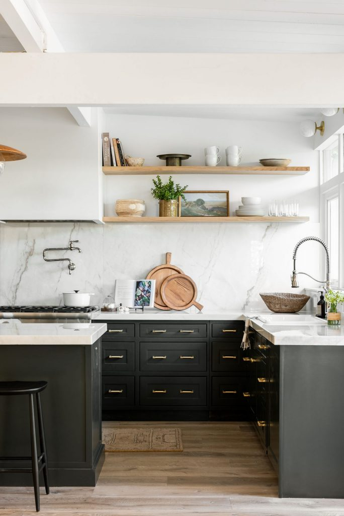 A beautiful kitchen with black and gold cabinetry, marble walls, and wooden shelves.