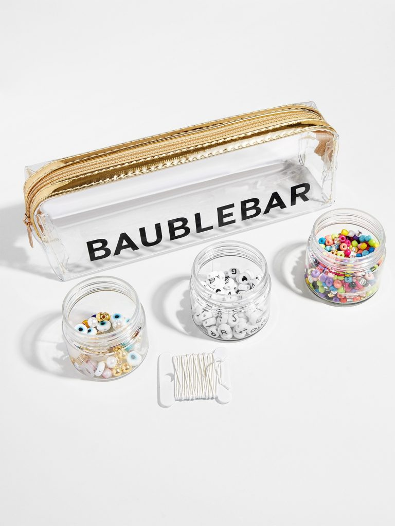 A clear case with jars of beads and string in front of it.
