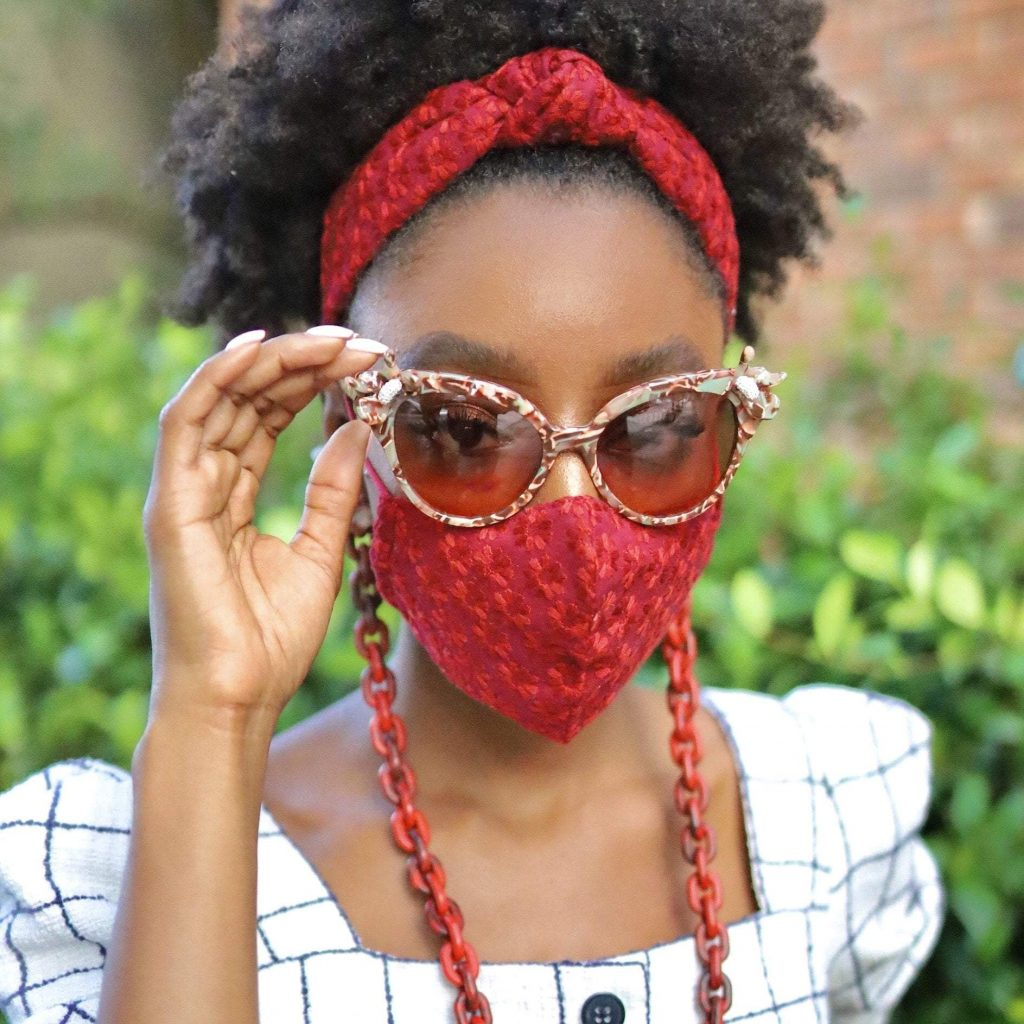 African American woman wearing a red mask with garnet tortoiseshell mask chain.