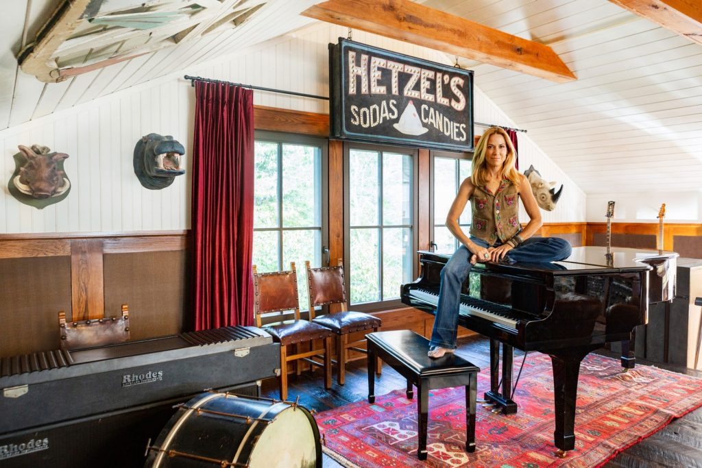 Sheryl Crow sitting on her grand piano at her at home music studio.