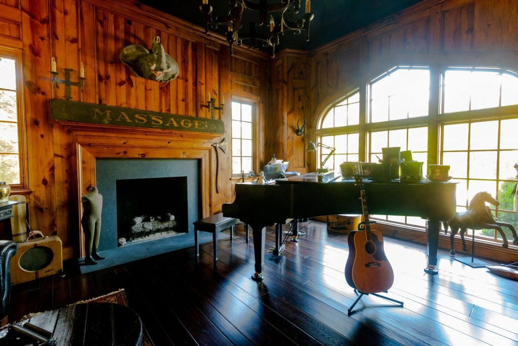 Music room with grand piano, wooden walls, fireplace, vintage signs, and guitar.