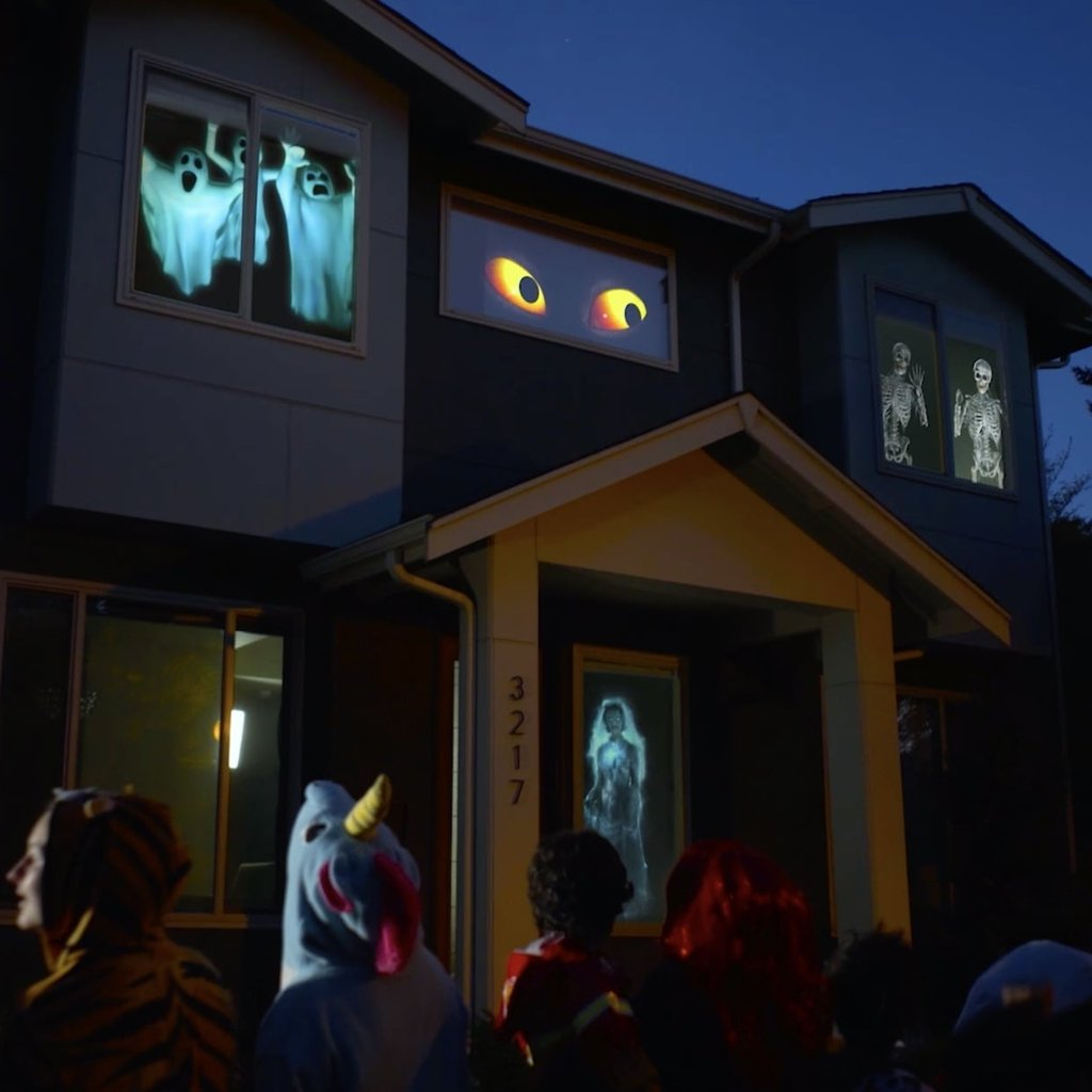 An exterior of a house with spooky images projected on it.