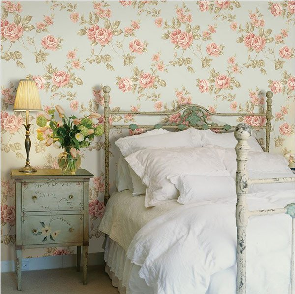 A shabby chic bedroom with a distressed bed frame and feminine floral wallpaper.