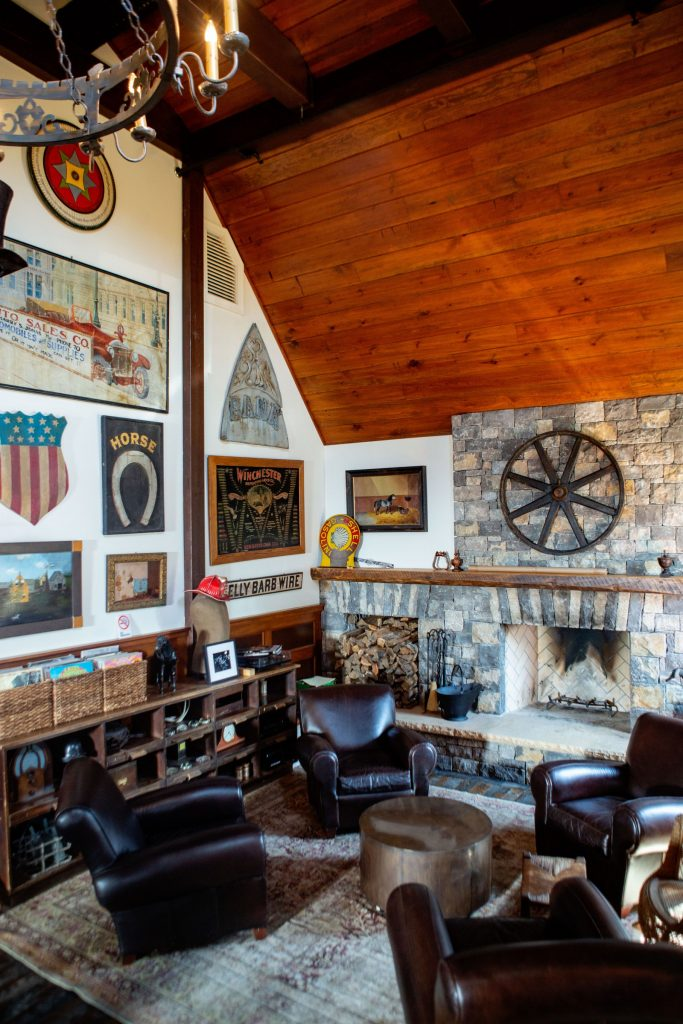 A sitting area of Sheryl's saloon with leather club chairs and vintage pieces covering the walls.