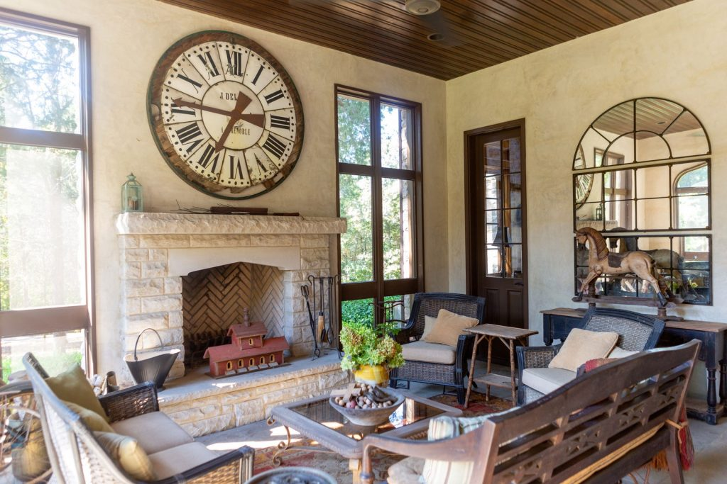 Screened in porch area with large vintage clock on wall, fireplace, and horse statue.
