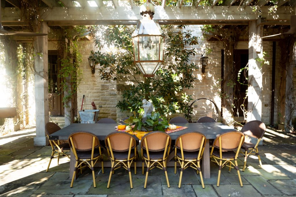 Outdoor dining room underneath pergola with a lot of greenery and large vintage light.