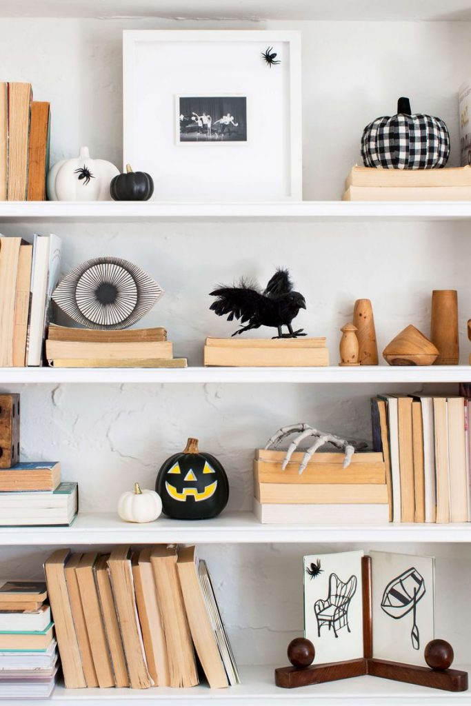 A white shelf with Halloween decor sprinkled throughout like pumpkins, a feathered crow, and skeleton hand.
