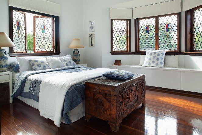 A traditional style bedroom with carved wooden chest at end of bed.